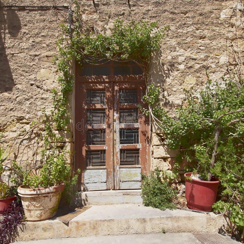 葡萄酒在石墙,雅典希腊上的房子门 库存照片