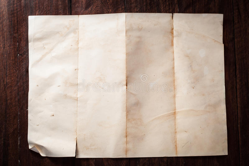 葡萄酒在黑暗的木桌上的打破的空的被折叠的和被弄皱的纸 库存图片