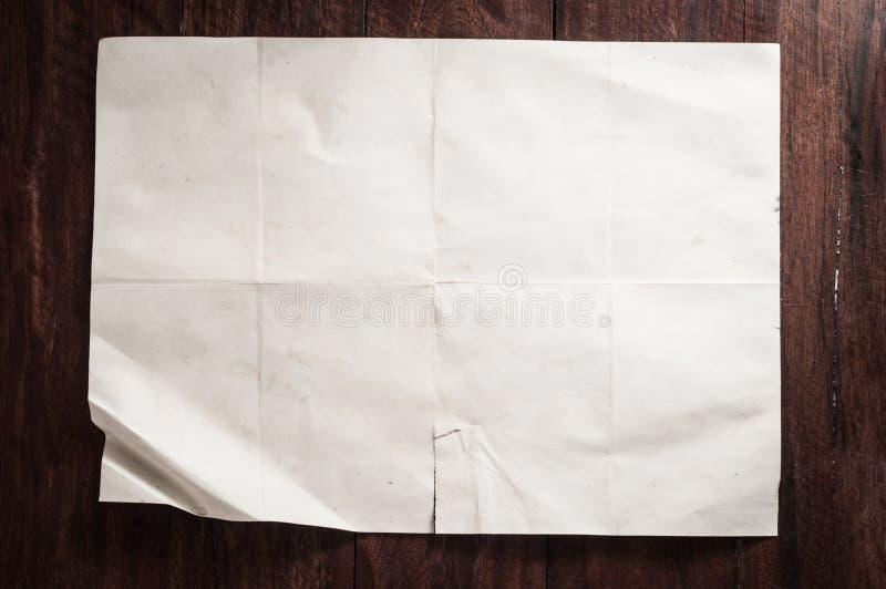 葡萄酒在黑暗的木桌上的打破的空的被折叠的和被弄皱的纸 免版税库存图片