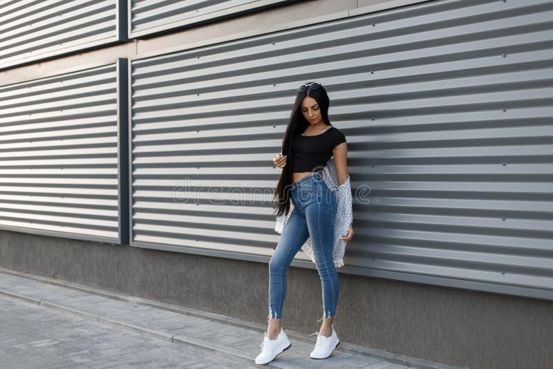 葡萄酒夏天夹克的美丽的俏丽的都市行家妇女在高的waisted牛仔裤的一件黑T恤杉在时髦运动鞋 库存图片