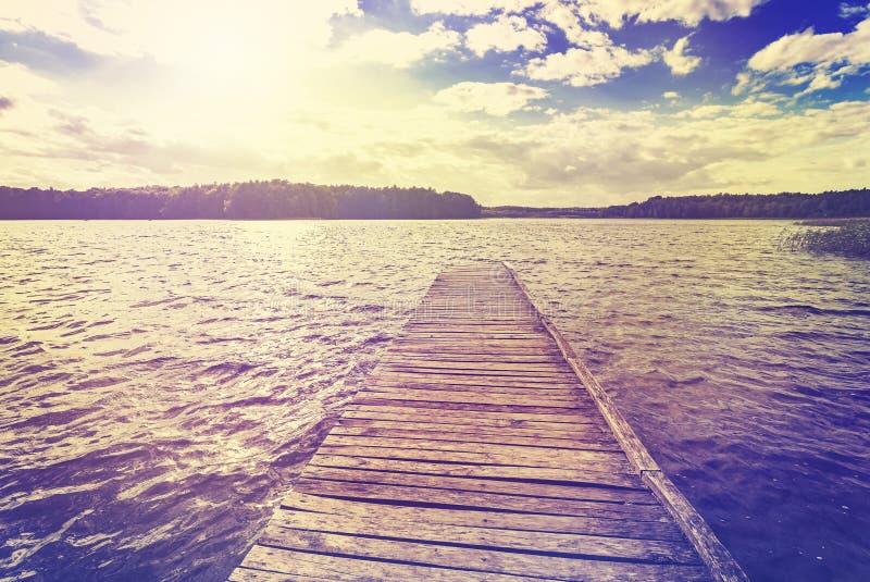 葡萄酒定了调子美好的日落照片在湖的 免版税库存照片