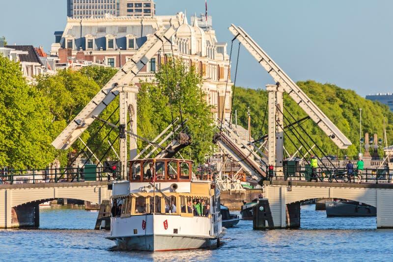 葡萄酒巡航小船通过著名阿姆斯特丹皮包骨头的桥梁 库存图片