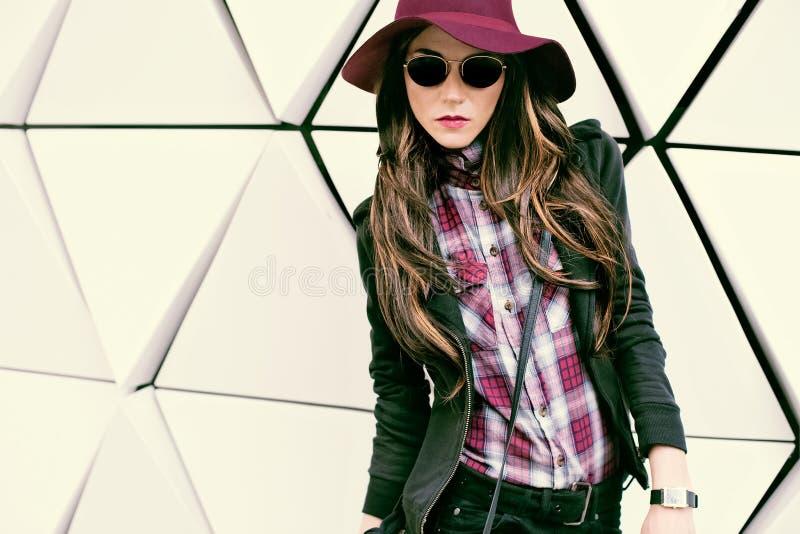 葡萄酒帽子和太阳镜的女孩在城市街道上 时尚猪圈 免版税库存照片