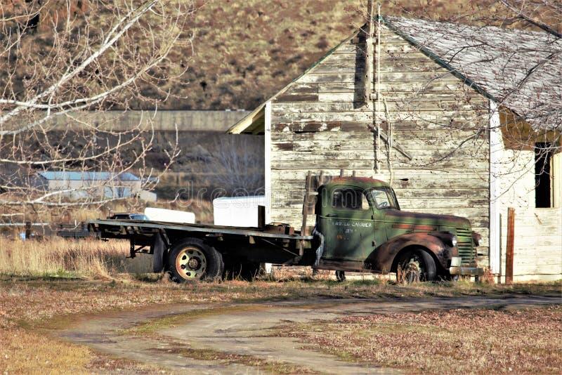 葡萄酒平板车大农场卡车在谷仓前面停放了 免版税库存照片