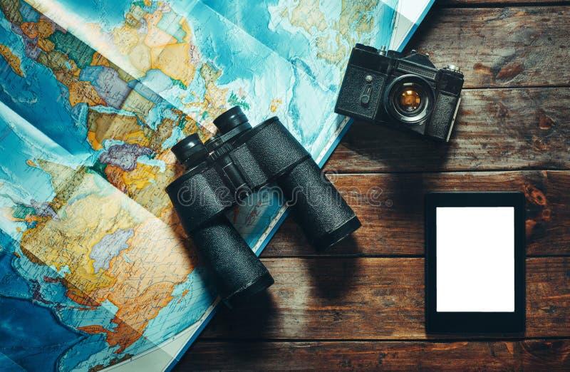 葡萄酒影片照相机、地图、片剂和双筒望远镜在木表,顶视图上 冒险旅行侦察员旅途概念 免版税库存图片