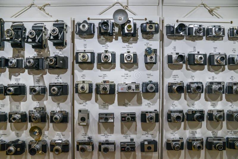 葡萄酒影片照相机在墙壁上按照年代次序排队了从20世纪20年代开始对20世纪60年代显示技术 库存照片