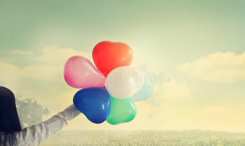 葡萄酒心脏与五颜六色的气球形状在手中在风景在夏天 库存照片