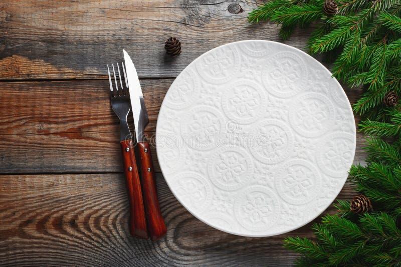 葡萄酒或土气圣诞节桌设置从上面 典雅的空的白色板材、利器和自然松树分支 免版税库存照片