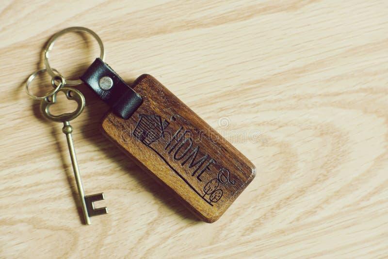 葡萄酒房子钥匙和木家庭keychain在木桌背景,关键性概念 免版税库存图片