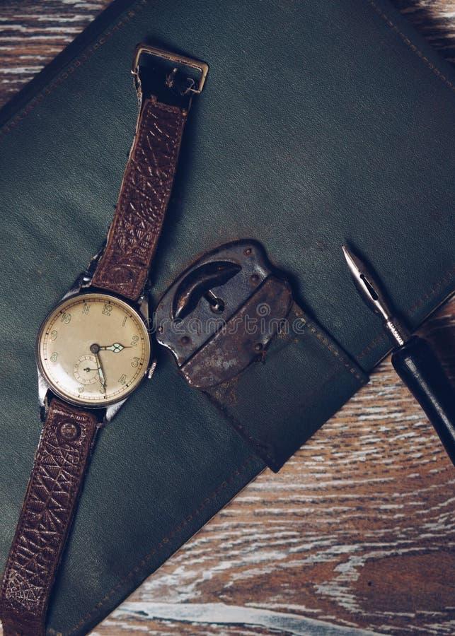 葡萄酒手表和老笔记本 免版税库存图片