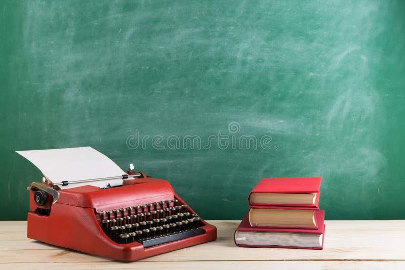 葡萄酒打字机和书在桌上与白纸在木书桌上 免版税库存照片