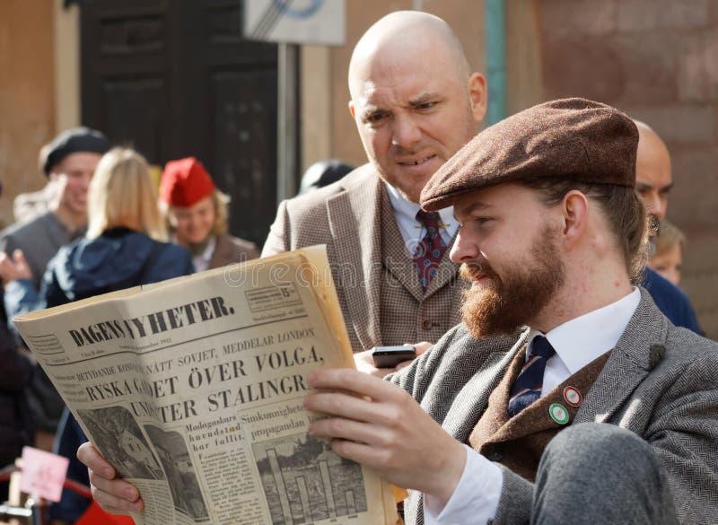 读葡萄酒报纸,佩带的古板的花呢c的两个人 库存图片