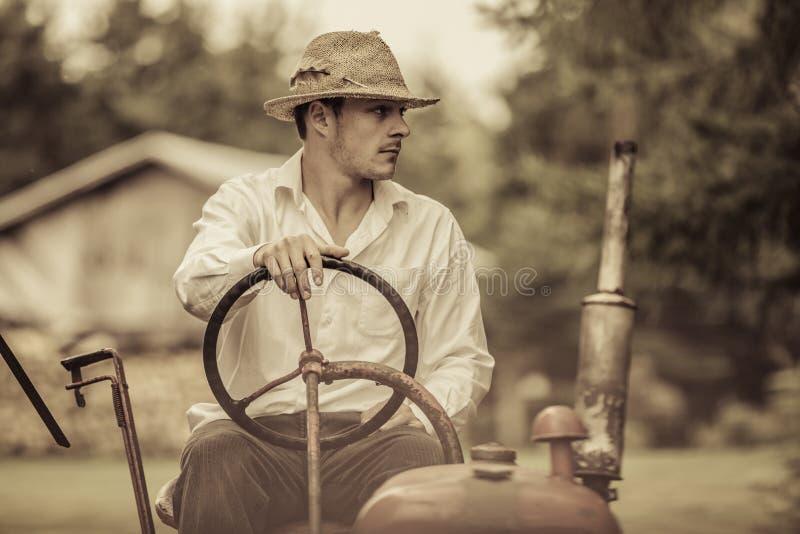 葡萄酒拖拉机的年轻农夫 库存图片