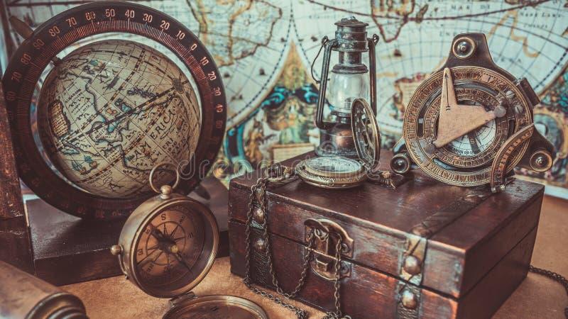 葡萄酒指南针木珍宝箱子灯照明设备和地球式样老海盗汇集照片 库存图片
