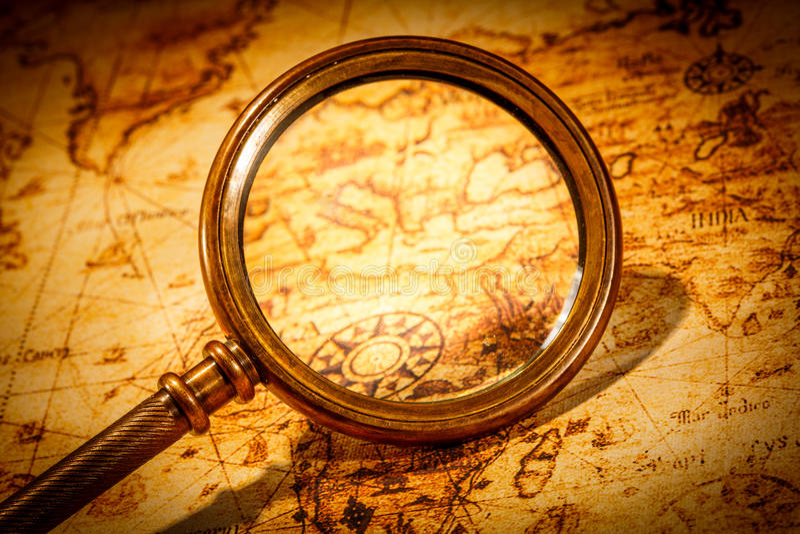 葡萄酒放大镜在一张古老世界地图说谎 图库摄影