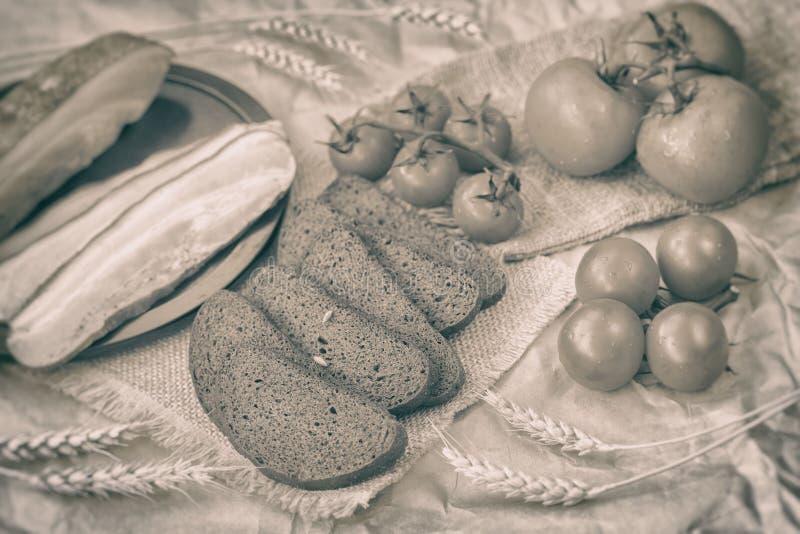 葡萄酒新鲜的有机食品乌贼属样式  快的传统鲜美快餐 切片烟肉,黑麦黑面包,成熟红色 免版税库存照片