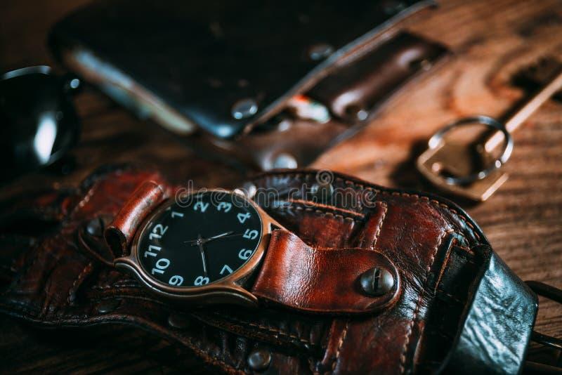 葡萄酒有皮革表带、钱包和钥匙的手手表在木背景 图库摄影