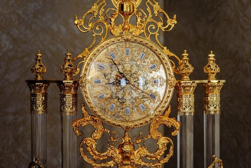 葡萄酒有罗马数字的被镀金的地板时钟在拨号盘 免版税库存图片