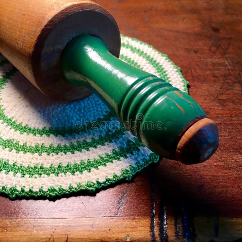 葡萄酒有绿色把柄的滚针在葡萄酒钩编了编织物握持热锅的布垫子 免版税图库摄影