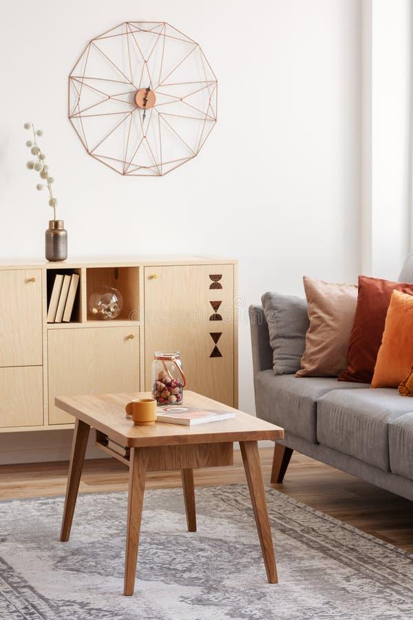 葡萄酒木咖啡桌和洗脸台在典雅的客厅内部与灰色长沙发 免版税库存图片
