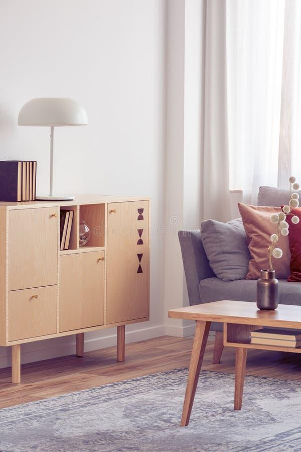 葡萄酒木咖啡桌和洗脸台在典雅的客厅内部与灰色长沙发 库存照片