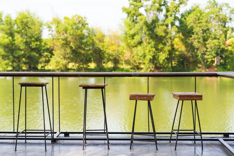 葡萄酒木桌和椅子在河背景 库存照片