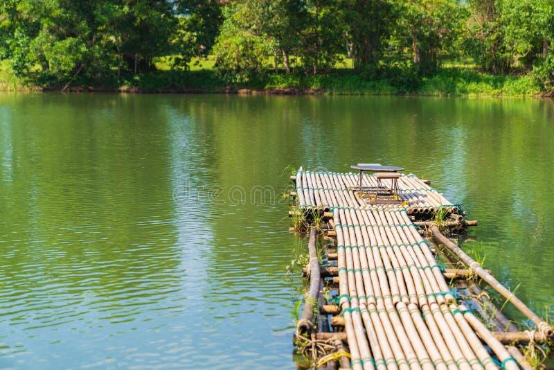 葡萄酒木桌和椅子在河背景 库存图片