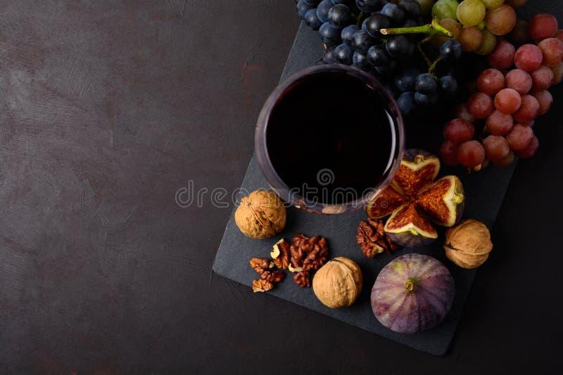 葡萄酒杯用红葡萄酒、说谎在黑暗的木背景的葡萄、无花果和核桃 顶视图 免版税库存图片