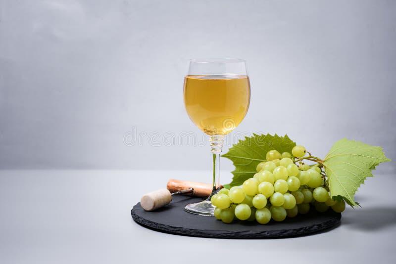 葡萄酒杯白酒用葡萄、黄柏和拔塞螺旋在灰色背景 假日庆祝概念 免版税库存图片