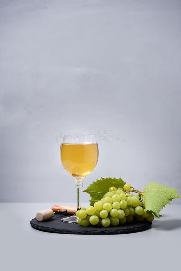 葡萄酒杯白酒用葡萄、黄柏和拔塞螺旋在灰色背景 假日庆祝概念 免版税库存照片