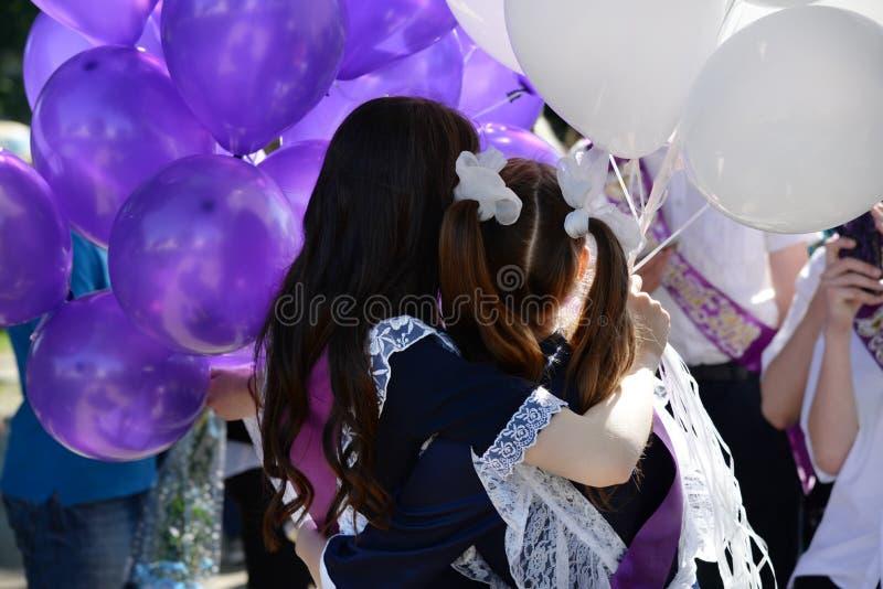 葡萄酒校服的两位女小学生有在毕业的气球的 库存照片
