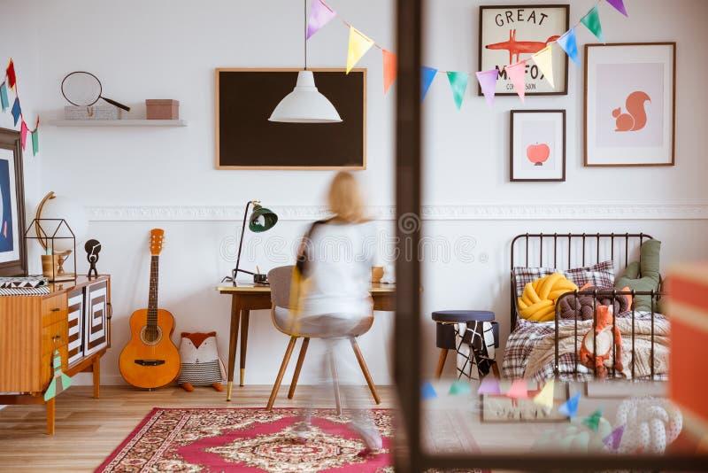 葡萄酒样式有床和书桌的儿童居室 免版税库存照片