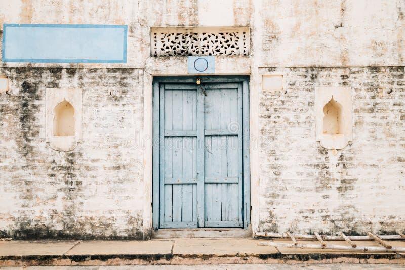 葡萄酒样式砖墙和蓝色木门,老印地安房子 免版税库存照片