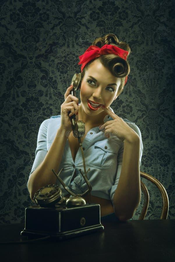 葡萄酒样式-妇女谈话在有减速火箭的拨号电话的电话 免版税图库摄影