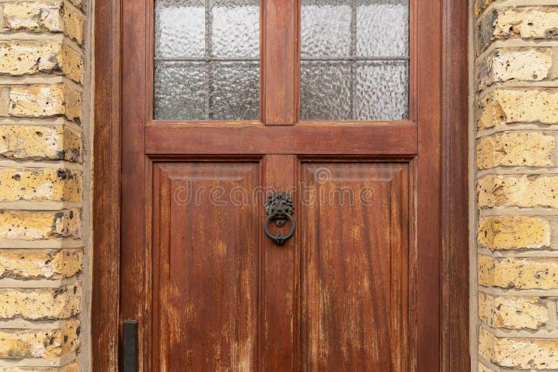 葡萄酒棕色被绘的门和敲门人狮子顶头看起来背景由古板的葡萄酒黄铜金属制成 免版税库存图片