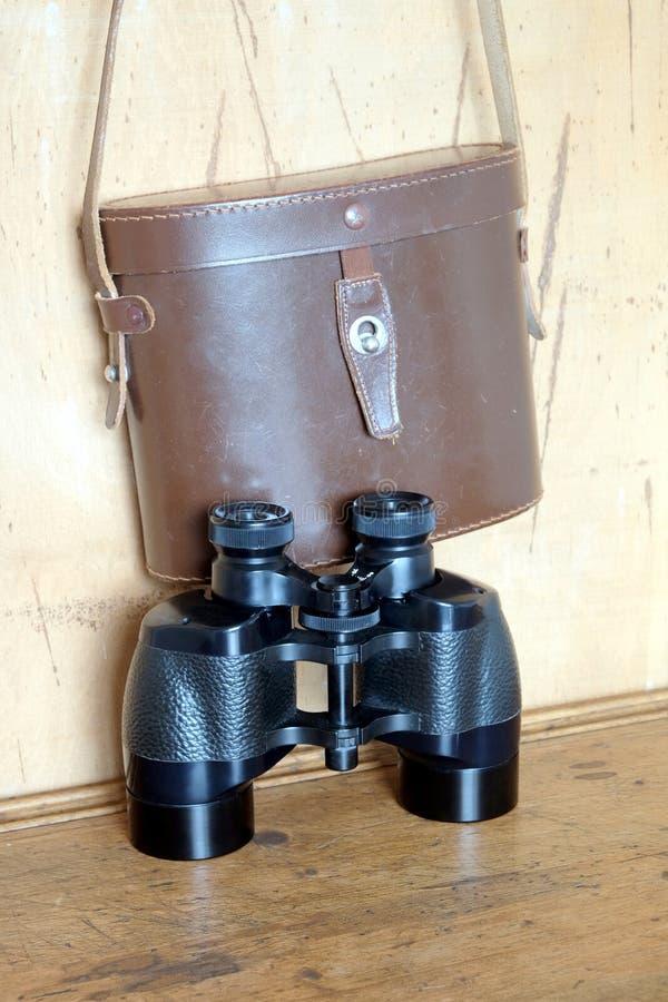 葡萄酒棱镜黑色颜色双筒望远镜和棕色皮革盒在墙壁上 图库摄影