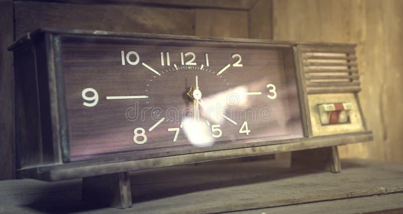 葡萄酒正方形在一张木桌上的台式时钟的减速火箭的被称呼的图象 免版税库存图片