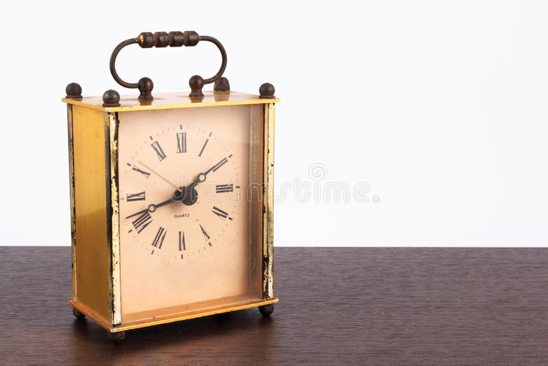葡萄酒正方形在一张木桌上的台式时钟的减速火箭的被称呼的图象 图库摄影