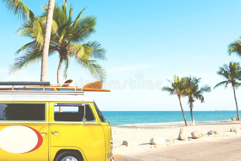 葡萄酒汽车在与一个冲浪板的热带海滩海边停放了在屋顶 免版税库存图片