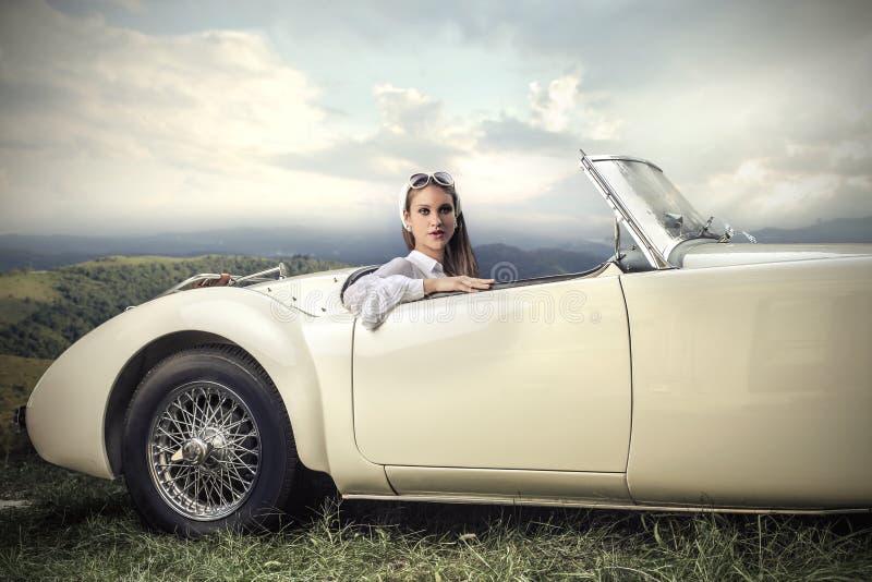 葡萄酒汽车的妇女 免版税库存照片