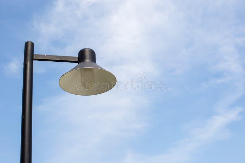 葡萄酒灯和杆的关闭在庭院公园和blie天空背景中 电子光夜 免版税库存照片