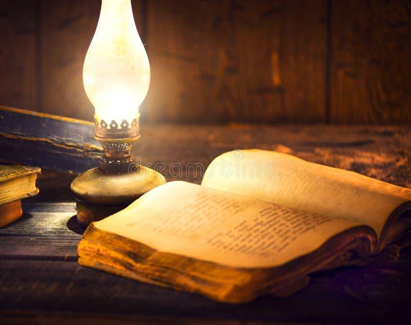葡萄酒煤油提灯和开放旧书 库存图片