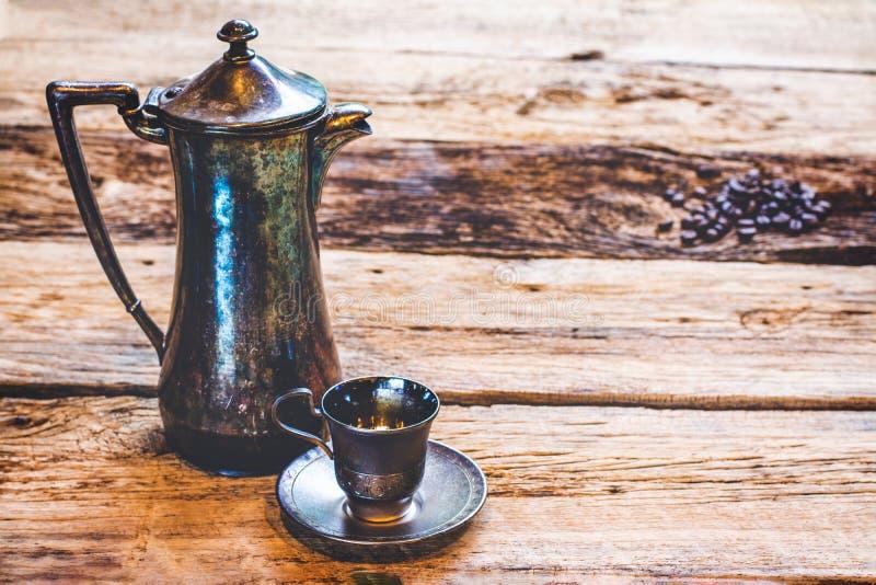 葡萄酒照片一个银色咖啡罐和一个银色浓咖啡杯子在木桌上 免版税库存照片