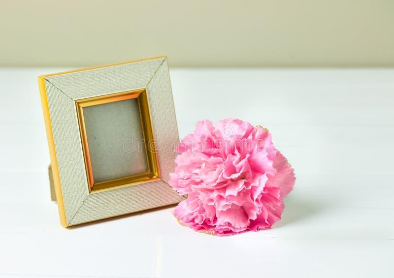 葡萄酒照片框架和桃红色康乃馨在木桌上开花 图库摄影