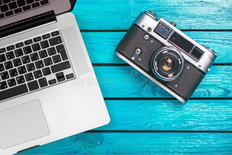 葡萄酒照片照相机和膝上型计算机在一张木桌上 图库摄影
