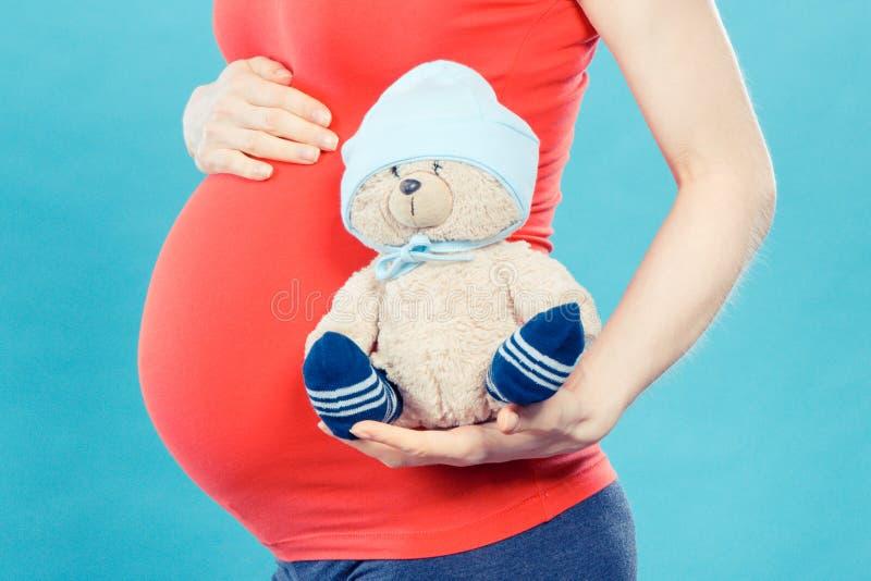 葡萄酒照片,怀孕的举行的玩具玩具熊的妇女,期望为婴孩概念 免版税图库摄影