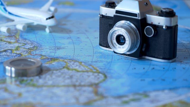 葡萄酒照相机和玩具在世界地图背景,计划飞行假期 免版税库存图片