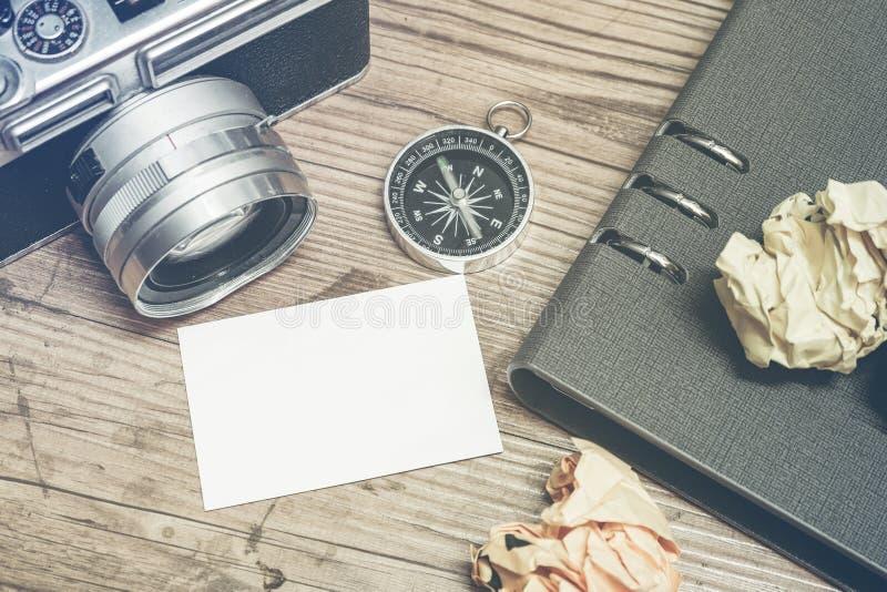 葡萄酒照相机,压皱纸、compas和计划者书布局在木地板上 免版税库存图片