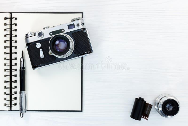 葡萄酒照相机,透镜,胶卷,与钢笔的开放笔记薄 免版税库存照片