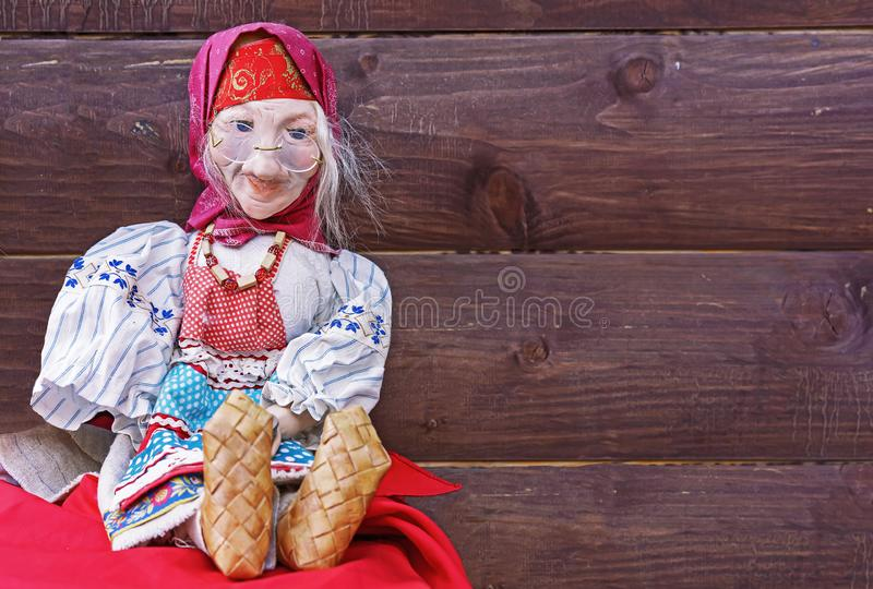 葡萄酒玩偶-一件全国俄国礼服和韧皮鞋子的一个灰发的祖母在棕色木背景 库存图片